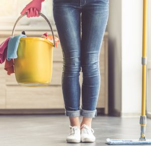Cleaning tips; Housecleaner with supplies in hand.